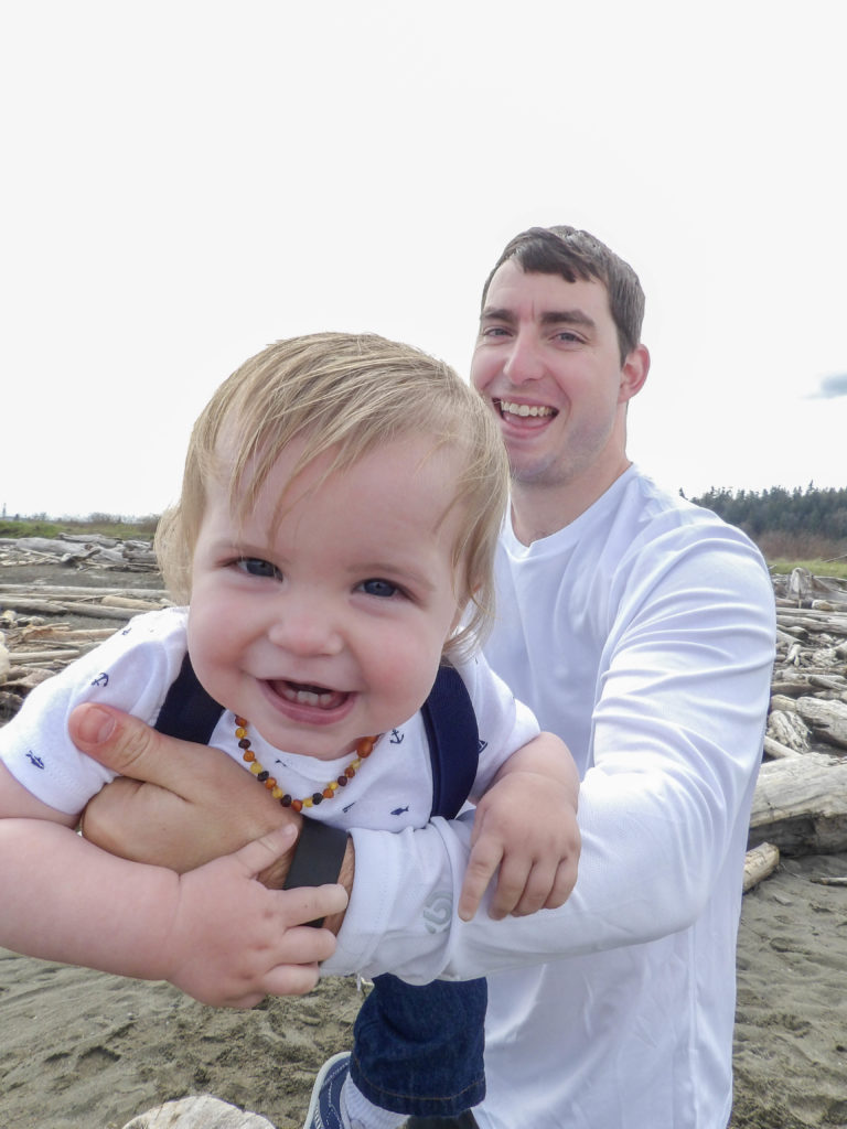 A baby boy being swung toward the camera by his dad, both of whom are smiling.