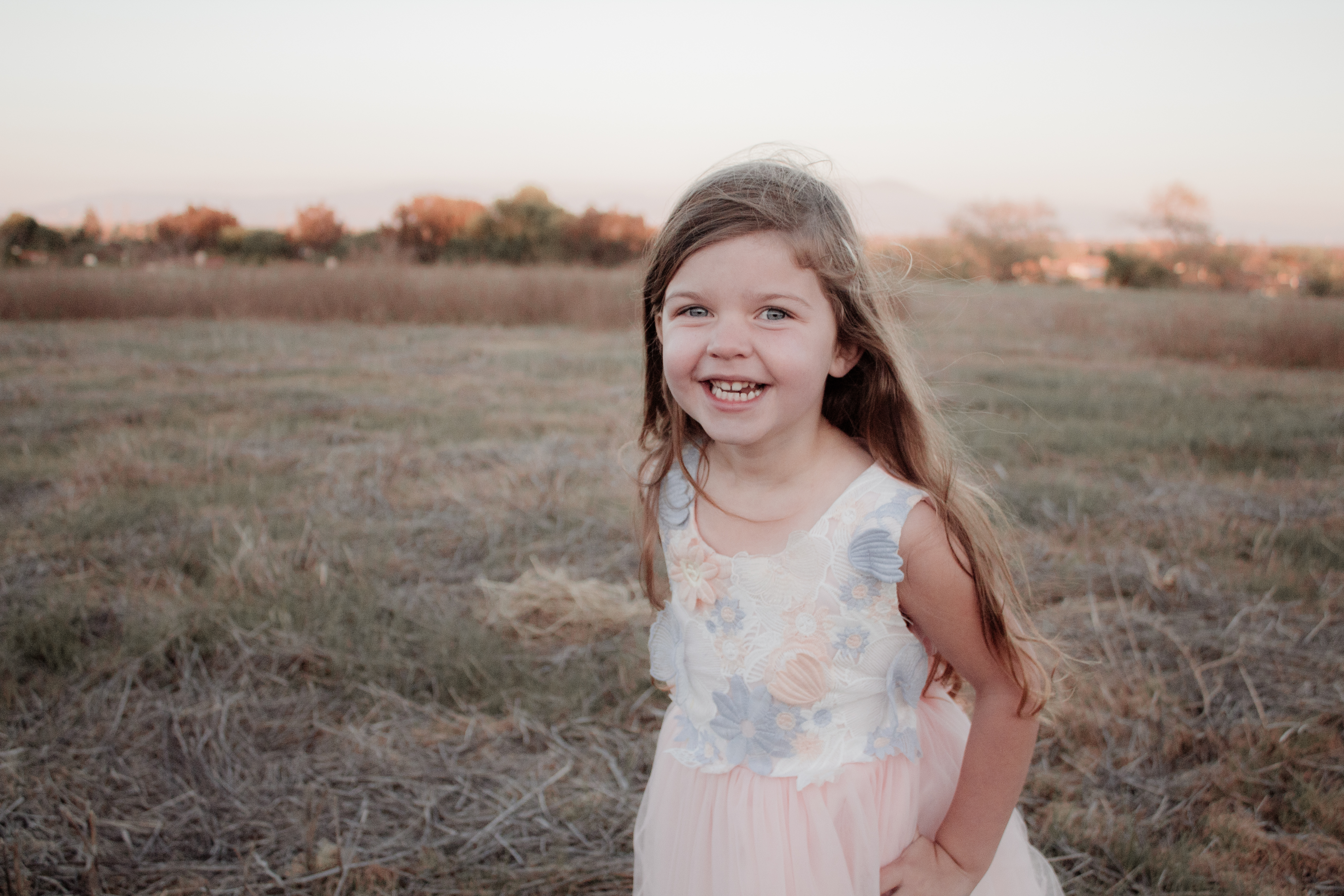 A photo of a little girl in a peach colored dress in a meadow.