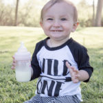 """A 1-year-old boy sitting in the grass holding a baby bottle. He is wearing a shirt that says """"Wild One."""""""