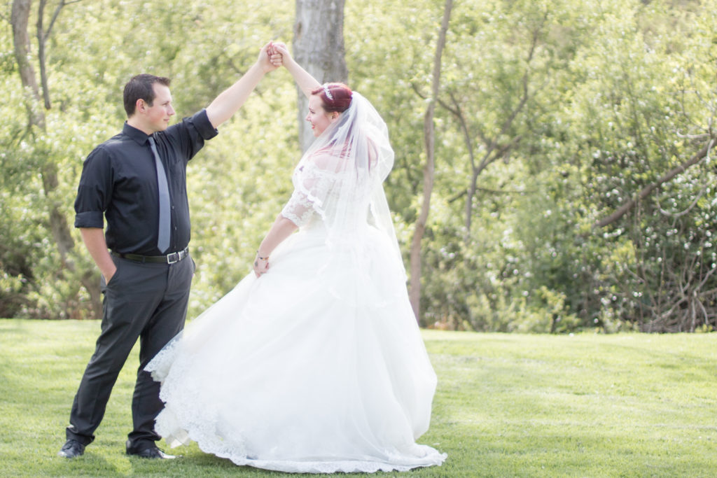 A bride and a groom in a wooded area. The groom is twirling the bride.