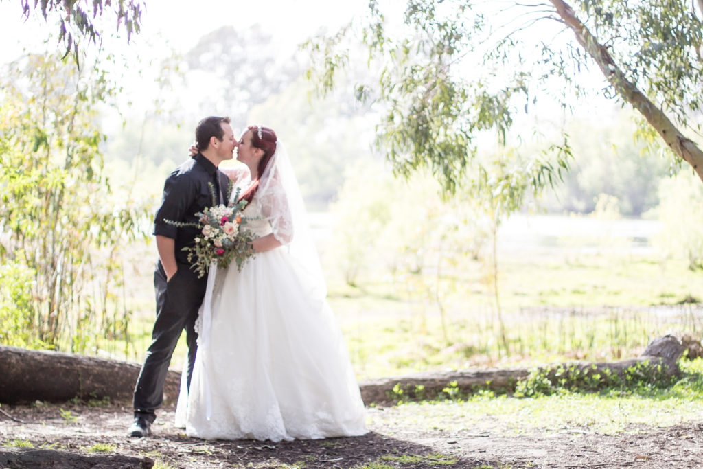 A bride and groom in a wooded area in front of a lake. The bride is holding a bouquet, and they are about to kiss.