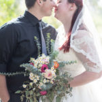 A bride and groom about to kiss. The bride is holding a bouquet.