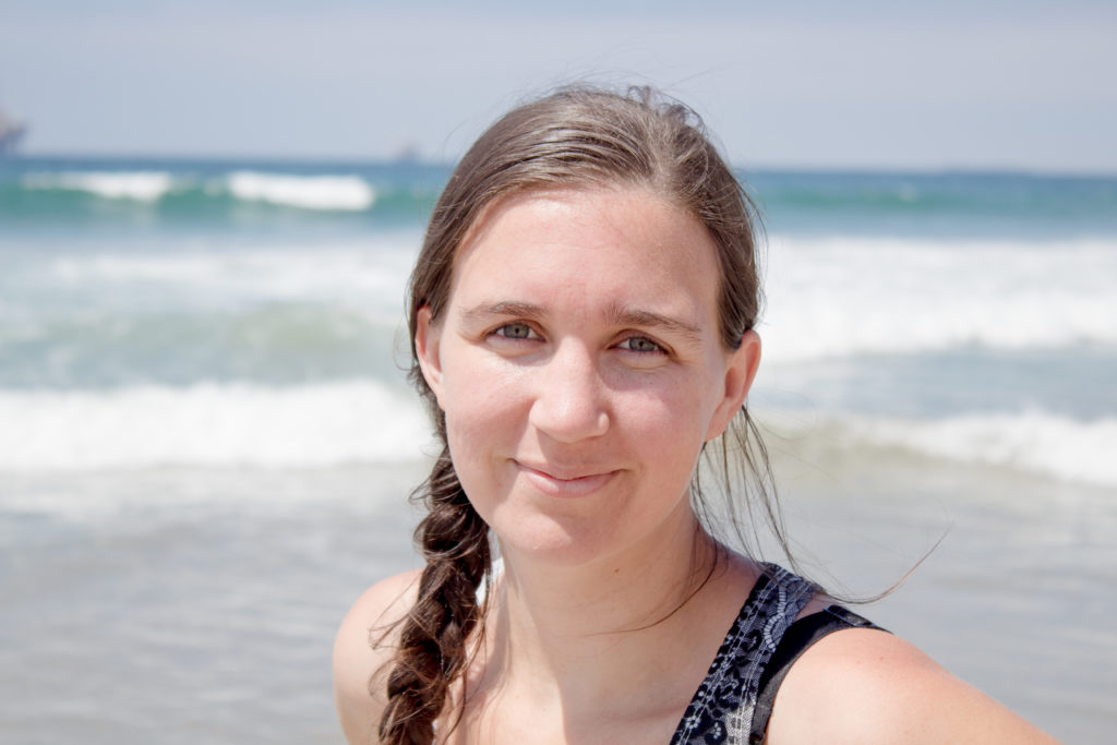 A photo of a woman in her 20s at the beach. It's a closeup of her shoulders and head. She has brown hair, blue eyes, and her hair is braided.