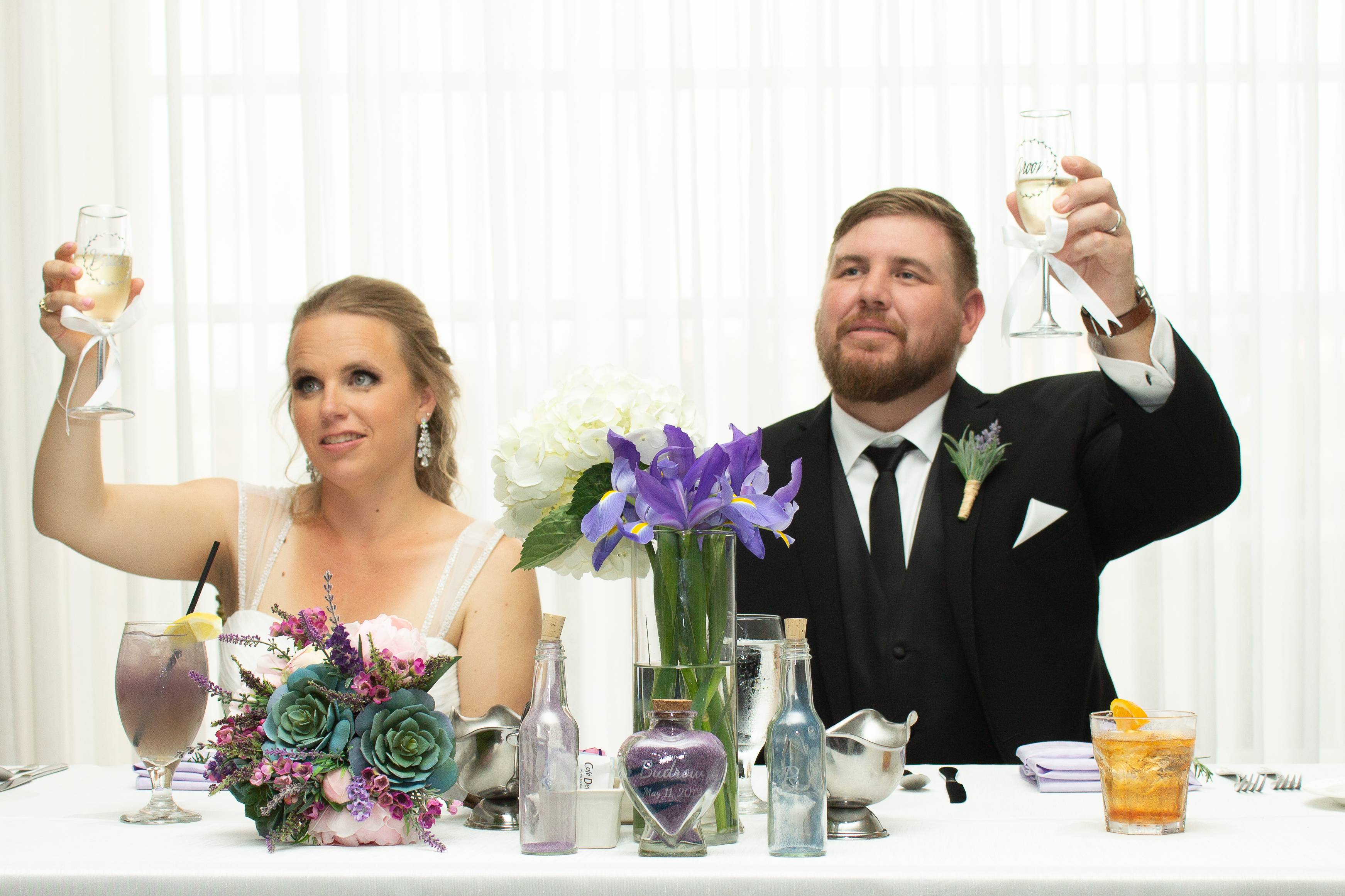 A bride and groom holding their champagne glasses up to toast. They are seated at a white-draped table with a centerpiece of purple iris. Also on the table is the bride's succulent, lavender, and soft pink bouquet.