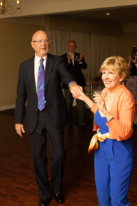 A man in a black suit and a woman in a blue jumpsuit with an orange shrug dancing. You can see the DJ in the background.