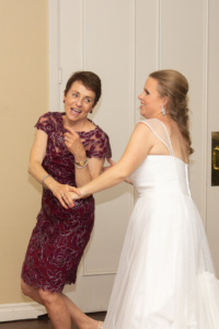 The bride and her mom (wearing a maroon lace dress) dancing together.