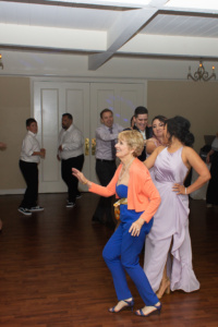 A lady in a blue jumpsuit with an orange shrug leading a conga line that contains several bridesmaids and groomsmen, among other people.