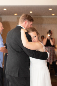 The bride and groom slow dancing on the dance floor.