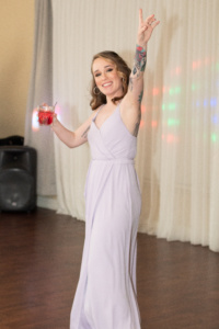 A bridesmaid in a lavender wedding dress dancing with a red drink in her hand. She is looking at the camera and smiling.