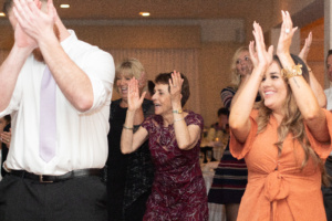 A photo of wedding guests dancing. They are all raising their hands and clapping.