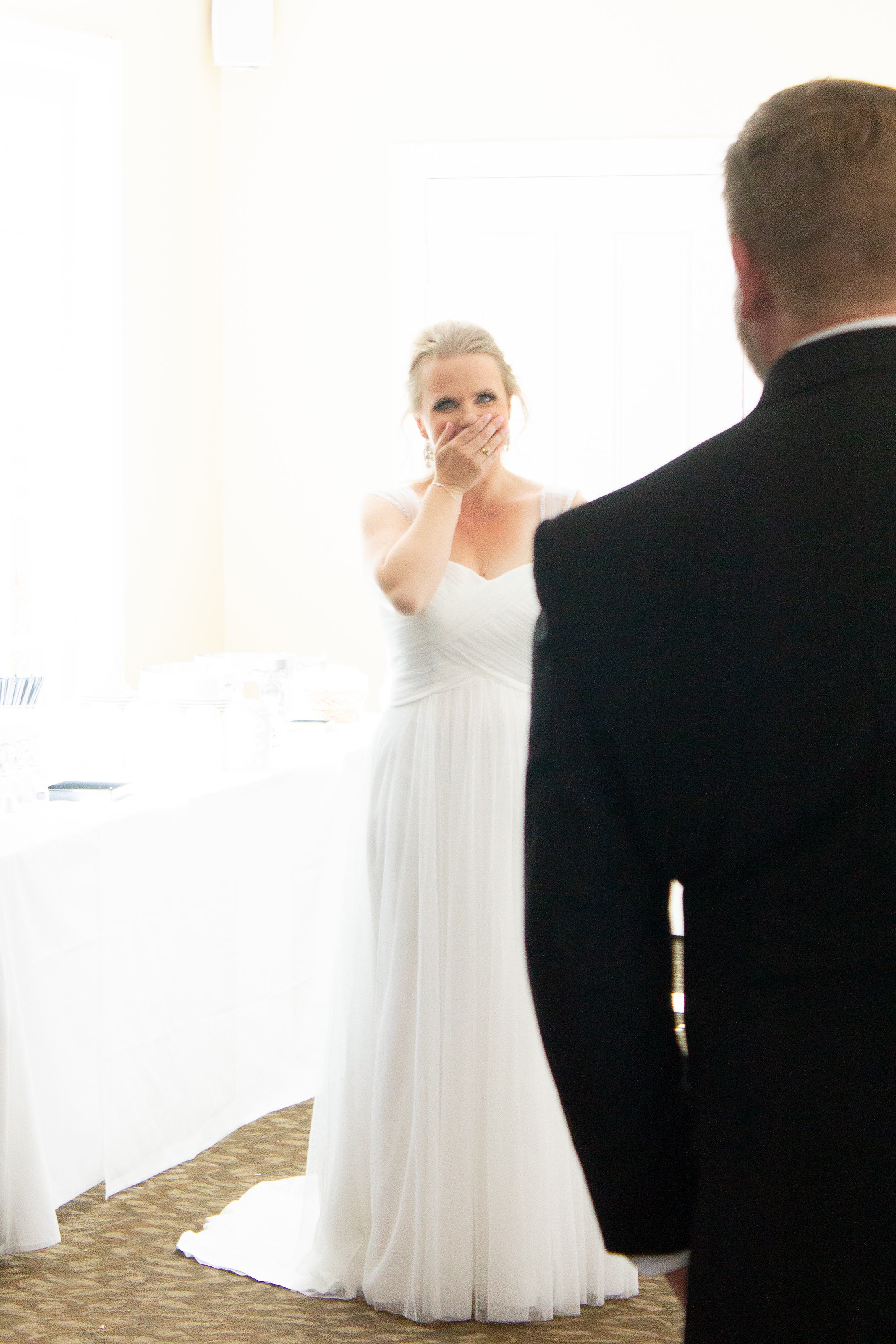 A bride covers her mouth in pleased surprise at seeing her groom in his wedding outfit for the first time.