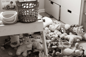 A black and white picture of a kid's bedroom with toys all over the floor and baskets on the table.