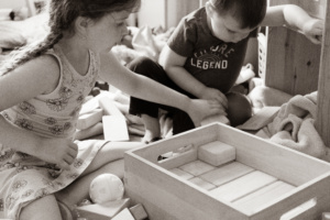 A black and white picture of two small kids putting wooden blocks away.