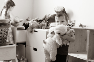 A black and white picture of a little boy holding an armful of stuffed animals. In the background his older sister is putting stuffed animals away in a drawer.