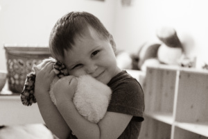 A black and white picture of a little boy hugging a stuffed owl.