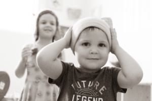 A black and white picture of a little boy putting on a cat hat. In the background is his older sister, also wearing a cat hat.