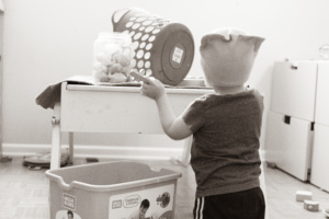 A black and white picture of a little boy cleaning his room in a cat hat.